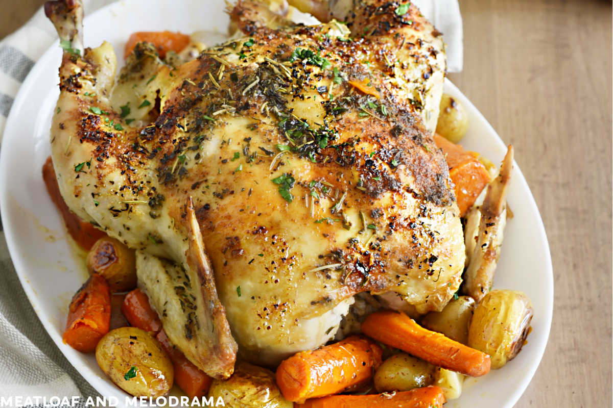 easy roast chicken with carrots and potatoes on a white platter