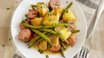 kielbasa sausage with baby potatoes and green beans on a white plate