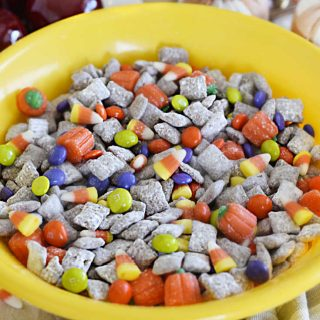 fall puppy chow muddy buddies in a yellow bowl with halloween candy