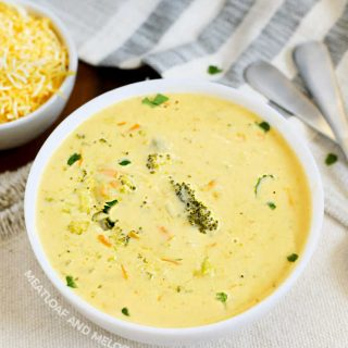 broccoli cheddar soup in a white bowl with shredded cheese on the side