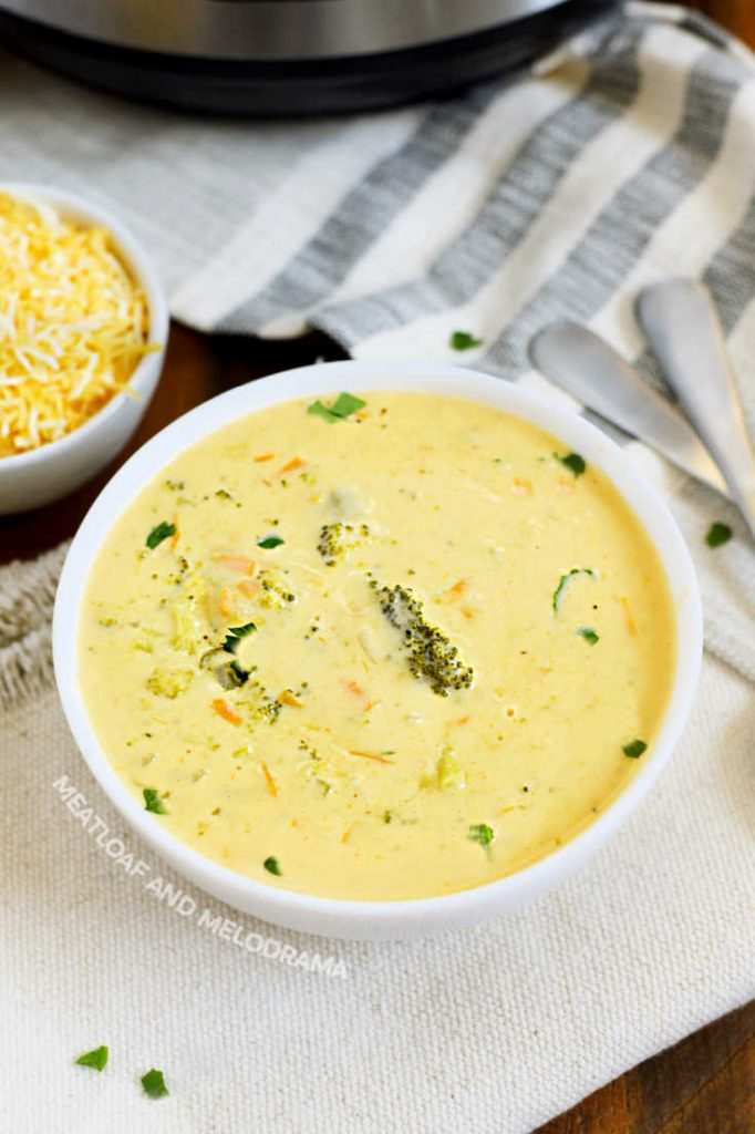 broccoli cheddar cheese soup in a white bowl with shredded cheese on the side