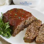 mom's onion soup meatloaf cut open on a white platter with parsley