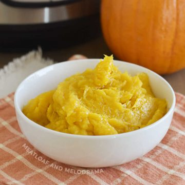 bowl of cooked pumpkin puree with instant pot pressure cooker and whole sugar pumpkin in background