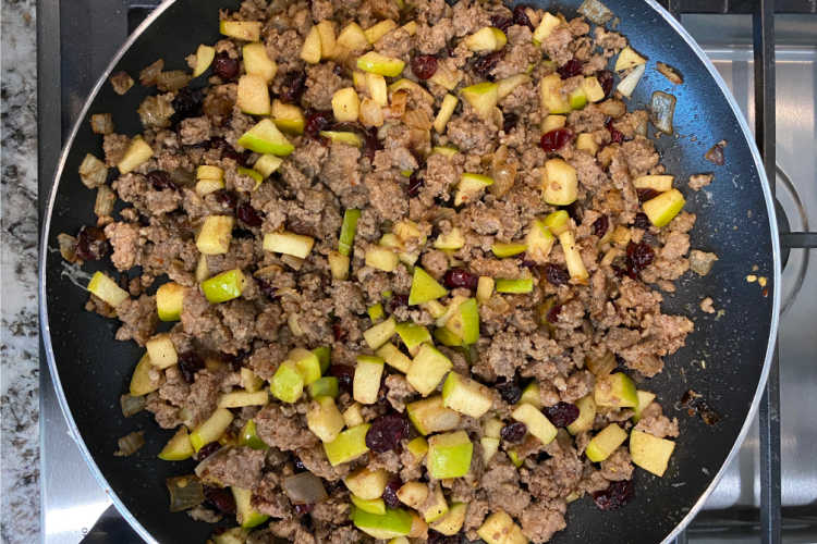sausage with apple cubes and cranberries in a skillet