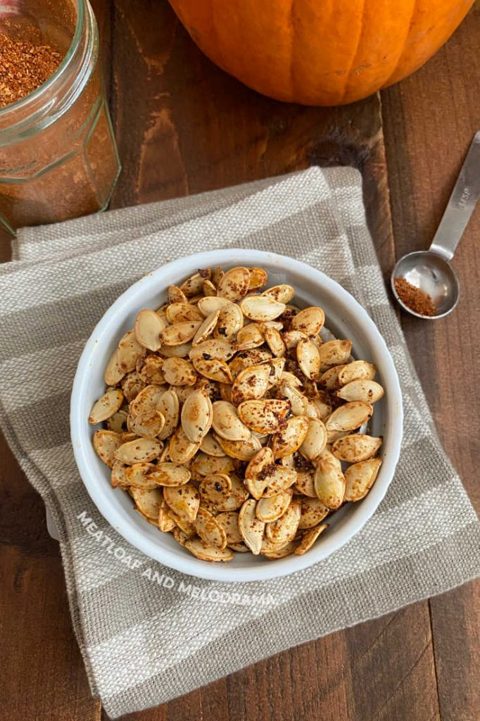 roasted pumpkin seeds in a white bowl with taco seasoning