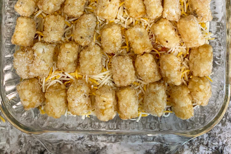 tater tots over mexican blend shredded cheese in a baking dish