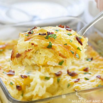 cheesy hashbrown potato casserole on a serving spoon with bacon