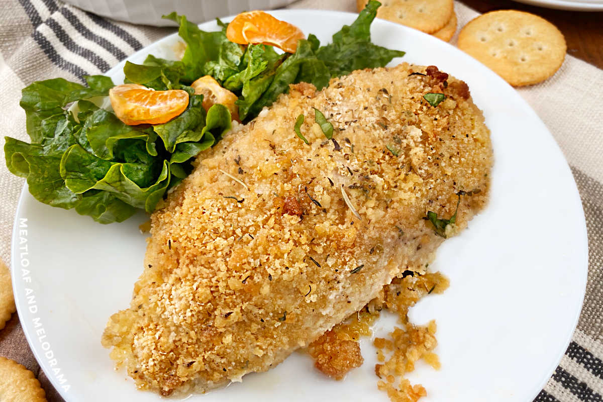 ritz cracker baked chicken breast on a white plate with salad