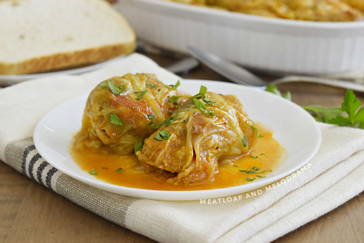2 stuffed cabbage rolls (halupki) on a white plate with tomato soup sauce