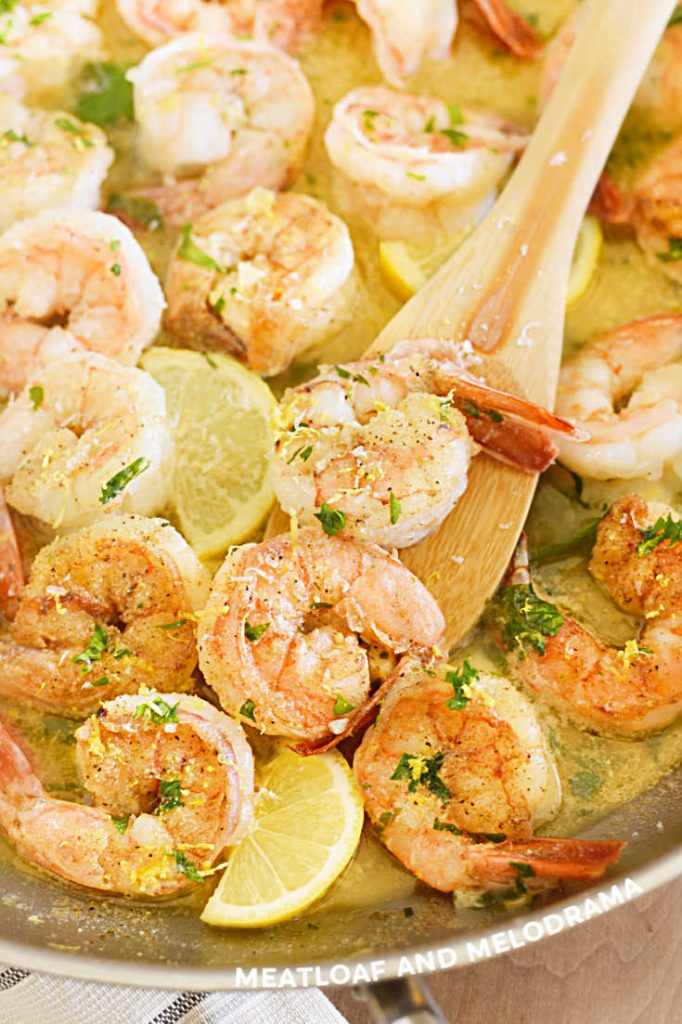 shrimp scampi with lemon slices in garlic butter sauce in skillet
