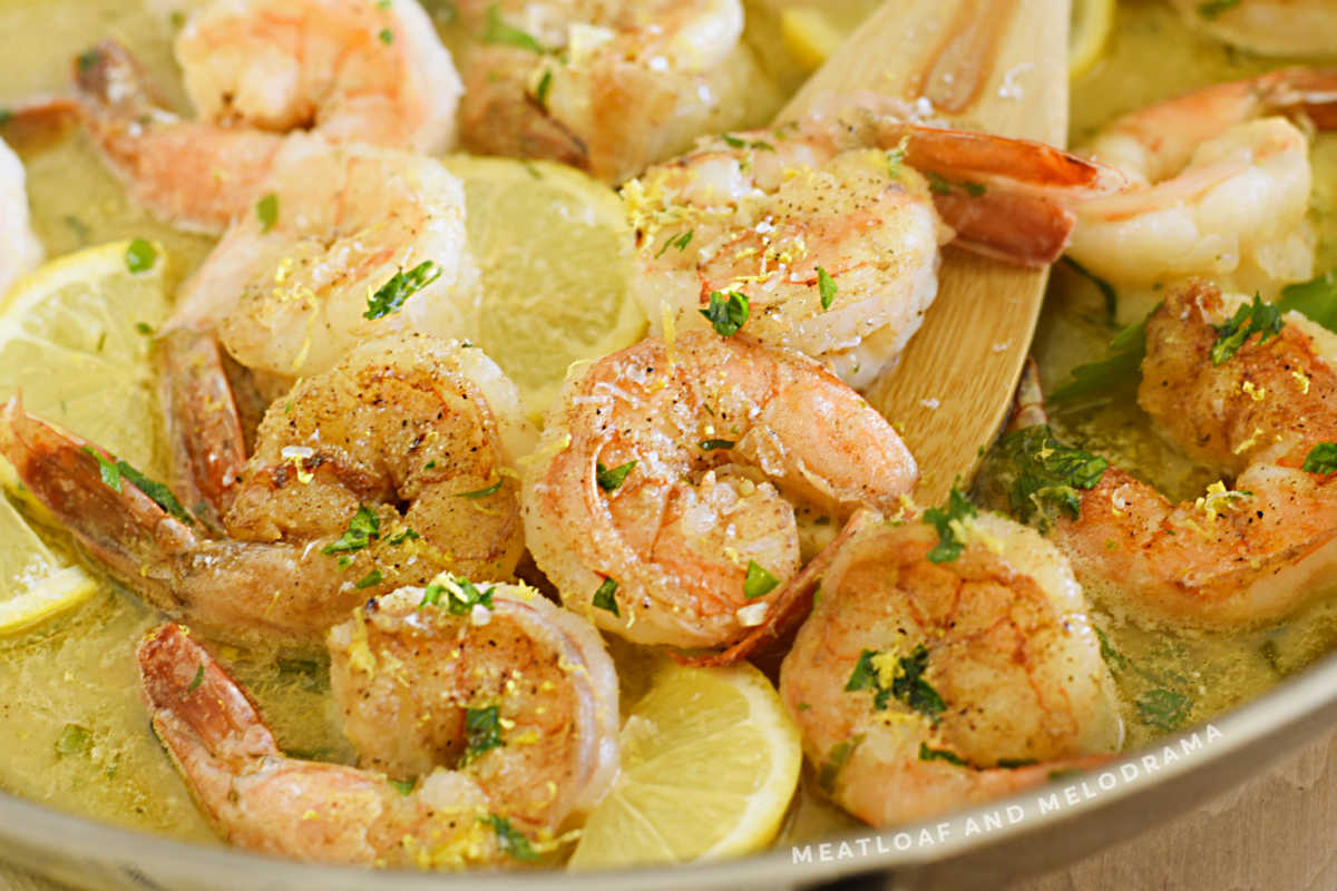 shrimp scampi in a pan with lemons and parsley