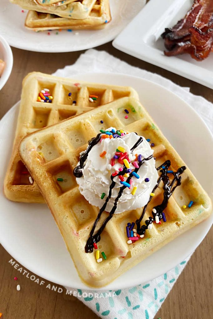 2 birthday waffles with sprinkles and whipped cream on a plate