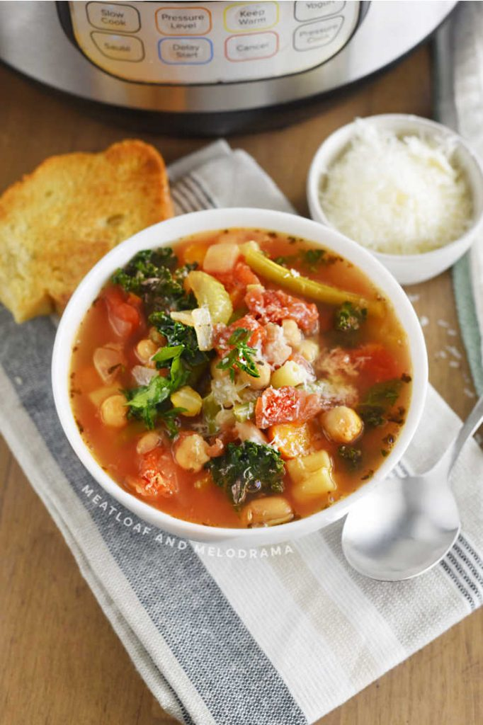 bowl of pressure cooker minestrone soup with tomatoes, kale, garbanzo beans and canellini beans and green beans