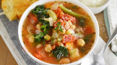 bowl of instant pot minestrone soup with garlic bread and parmesan cheese