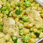 baked ranch chicken dinner with potatoes and broccoli on a sheet pan