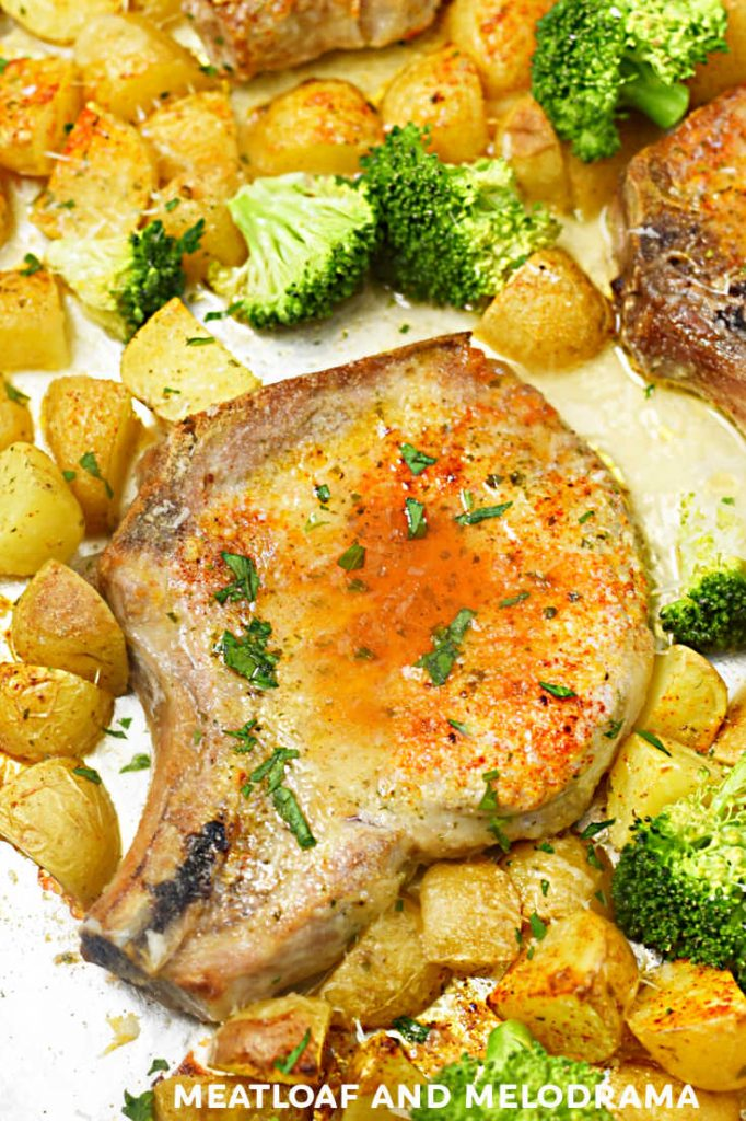 baked pork chop with paprika and potatoes and broccoli on a sheet pan