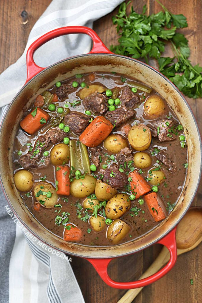 beef stew in red dutch oven with carrots and potatoes and parsley