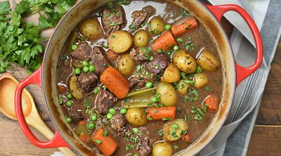 beef stew with potatoes and carrots in red dutch oven
