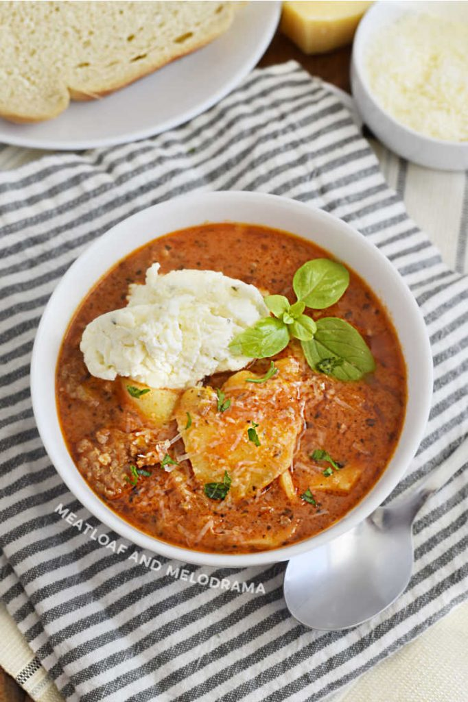 bowl of lasagna soup with ricotta cheese mixture on top
