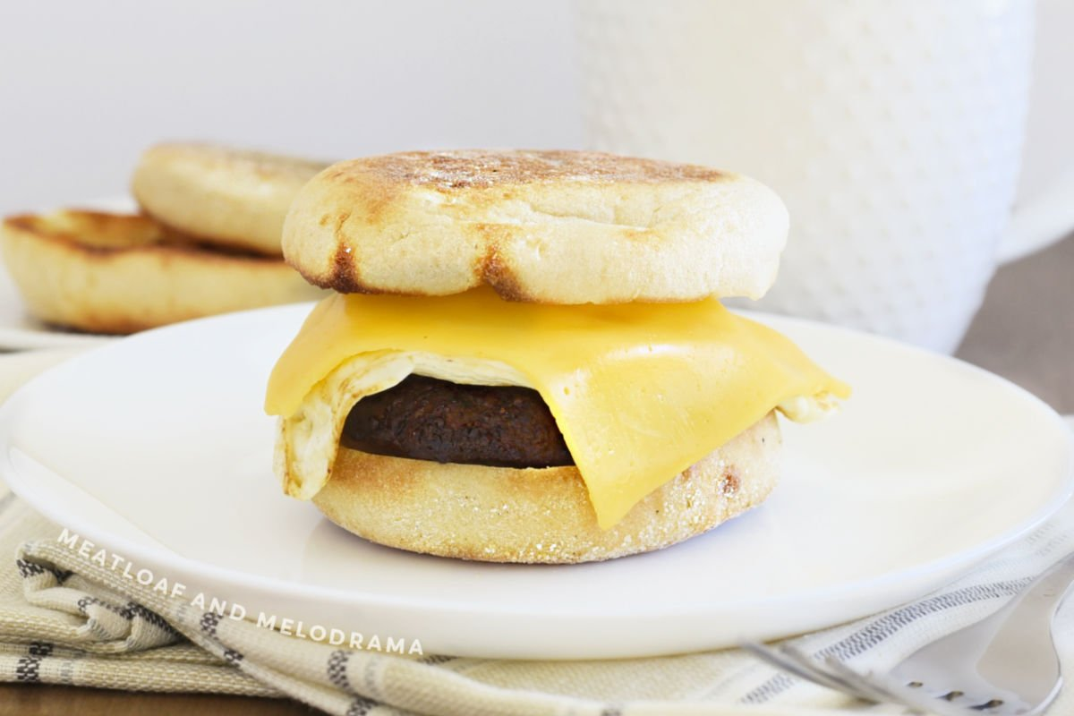 sausage egg and cheese breakfast sandwich on English muffin on a white plate