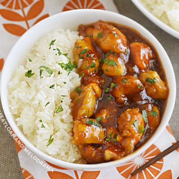 bowl of orange chicken with orange marmalade bbq sauce on the table with rice