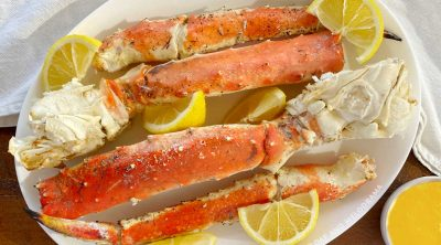 grilled king crab legs on a white platter with lemon wedges and melted butter