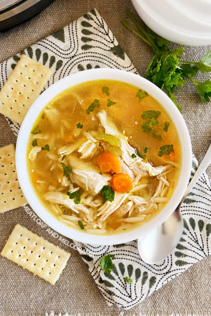 bowl of homemade pressure cooker chicken soup with carrots and parsley