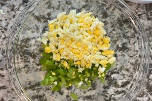 chopped hard boiled eggs and celery in a mixing bowl
