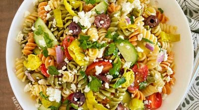Greek pasta salad with feta cheese in white serving bowl