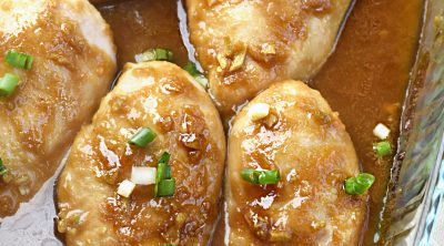 baked honey garlic chicken breasts with green onions in baking dish