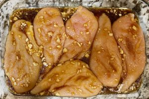 chicken breasts with garlic and honey soy sauce mix in a baking dish