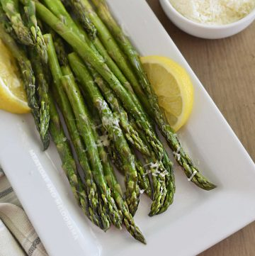 microwave asparagus on white platter with lemon slices and parmesan cheese