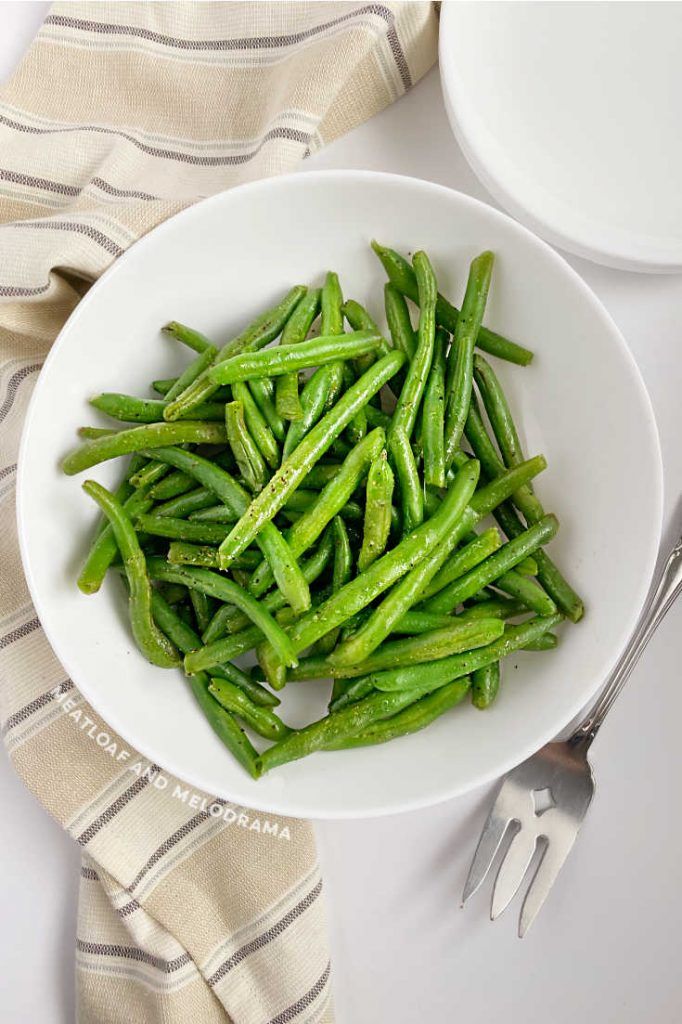 steamed green beans in white serving dish with fork