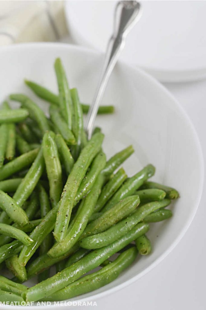 fresh cooked green beans in a white bowl