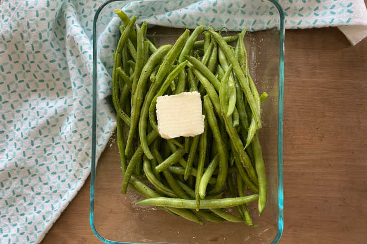 string beans in glass dish with butter