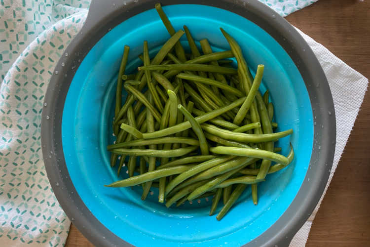 fresh green beans in blue colander